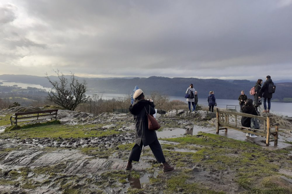 Tourists enjoy the view from Orrest Head, Windermere, the Lake District