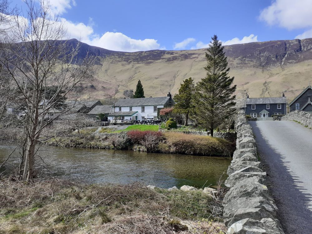 Cottage with river and mountains behind in Borrowdale