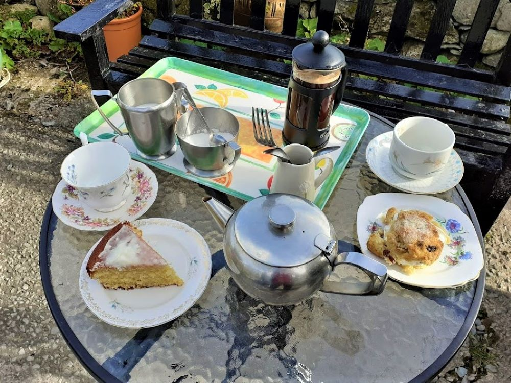 Table loaded with tea, coffee and cake